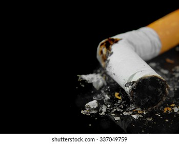 Macro image of a crushed cigarette butt on a black background is a quit smoking concept. Copy space for your message. Good for the Great American Smokeout Day in November or any lung cancer issue