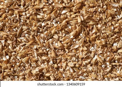A macro image detailing crushed malted barley grain. The primary ingredient in beer making, the malt is steeped and boiled to extract the fermentable sugars; which yeast in turn changes to alcohol.