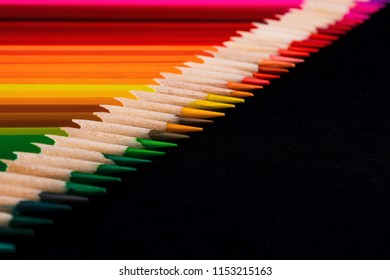 A macro image of a diagonal line of colored pencil sharpened tips with plenty of Black negative space for copy.  The line is very ordered and laid out in an OCD manner.