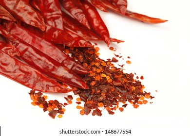 Macro image of dried Red hot cayenne Chilli Peppers and Flakes isolated on white Background