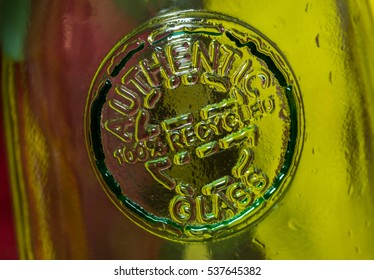 Macro image of an embossed logo on a 100% recycled glass bottle.