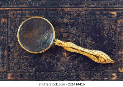 macro image of magnifying glass over antique black cover.