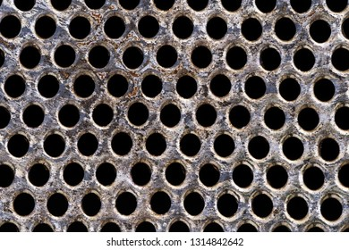 macro image of old metal kitchen strainer with holes