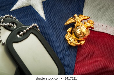 Macro image of the US Marine Corps emblem on the American flag next to military dog tags