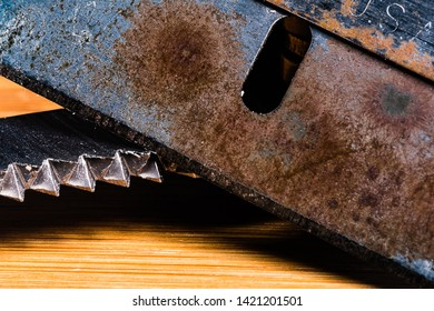A Macro image of A very old, dull and rusty razor with an equally dirty and used serrated blade.