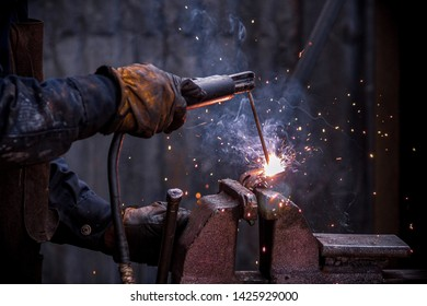 Macro industry and construction worker welding metal creating light sparks and smoke with a blurry and dark industry background