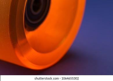 A macro of a longboard roll in orange on blue underground