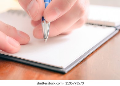 Macro Of A Male Hand Writing In A Blank Organizer With A Biro