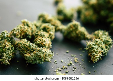 Macro of marijuana bud with trichomes and crushed weed for chopping a canabis on a black table close up