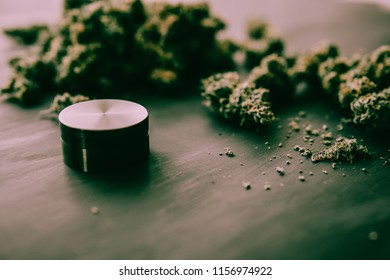 Macro of marijuana with trichomes and crushed weed in a grinder for chopping a canapis on a black table
