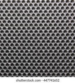 Macro of metal panel with holes on a loudspeaker.