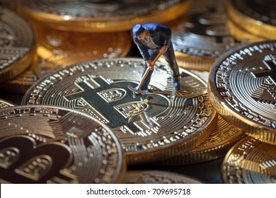 macro miner figure working on group of bitcoins. virtual cryptocurrency mining concept