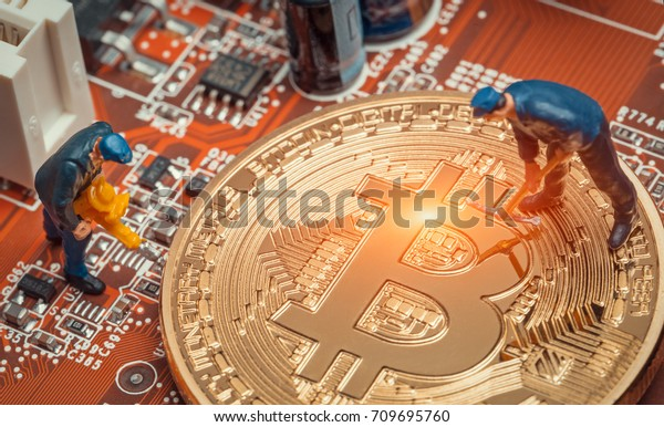 macro miner figures working on a bitcoin on computer motherboard