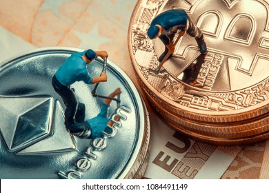 macro miner figurines working on stack of bitcoin and ethereum placed on euro banknotes. virtual cryptocurrency mining and trading concept