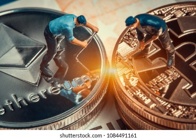 macro miner figurines working on stack of bitcoin and ethereum placed on euro banknote. virtual cryptocurrency mining and trading concept