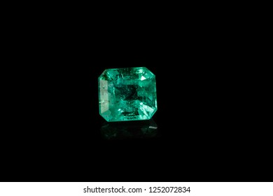 Macro mineral Emerald gemstone faceted on black background close up