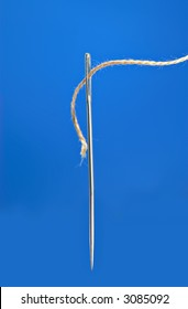 A macro of a needle and thread ready for sewing