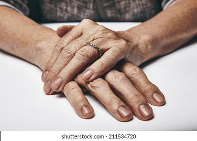 Macro of an old lady sitting with her hands clasped on a table. Elderly woman's hands with a ring resting on grey surface. Focus on hands.