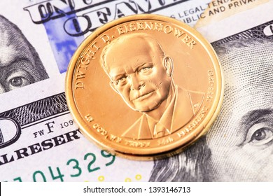 macro one dollar golden coin with Dwight D. Eisenhower portrait, and hundred dollars banknotes