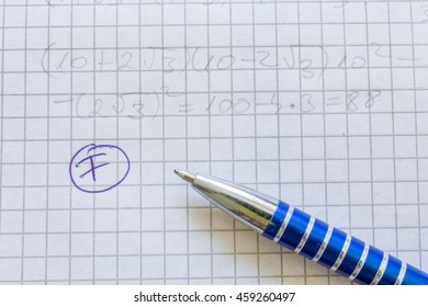 Macro of a paper with math formulas and  pen. F grade