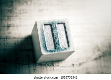 Macro Of A Pause Icon On A Wooden Block On A Table
