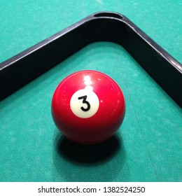 Macro Photo of a billiard ball. Red billiard ball with the number 3. Red billiard ball on a green table.