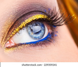 Macro photo of blue eye looking away. Professional make up on eye with blue and gold colors. Studio shot