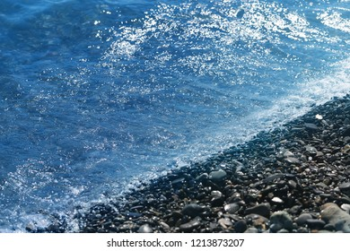 Macro photo of blue sea waves with foam on the beach