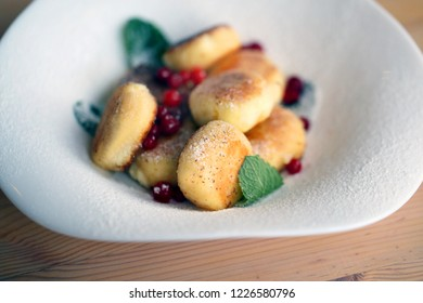 Macro photo of bright tasty cheese cakes with berries on a light background