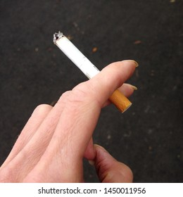 Macro photo of cigarette in hand. Background smoking cigarette in hand. Image of smoking a cigarette
