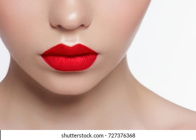 The macro photo of the closed female mouth. Chubby lips with red lipstick show a fashionable make-up and increase in lips. Cosmetology, Spa, cosmetics