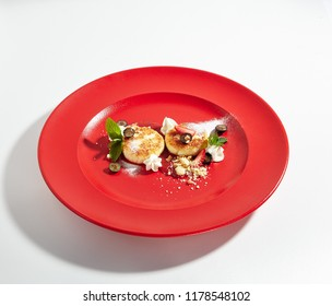 Macro Photo of Cottage Cheese Pancakes with Berry Sauce and Homemade Sour Cream on Elegant Restaurant Red Plate Isolated on White Background. Quark Pancakes, Tvorozhniki or Syrnyky Close Up