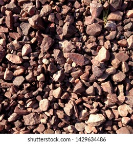 Macro photo of crushed stone and gravel on the ground. Texture background brown  stones on a black earth background. Image of broken stones and gravel