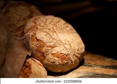 Macro photo of delicious big round baked bread on a wooden surface