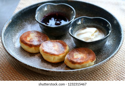 Macro photo of delicious bright cheese cakes with jam and sour cream on a dark plate in a restaurant