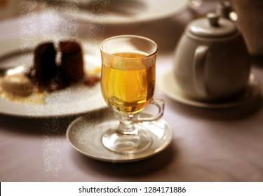 Macro photo of delicious green tea in a glass with cake on a white table