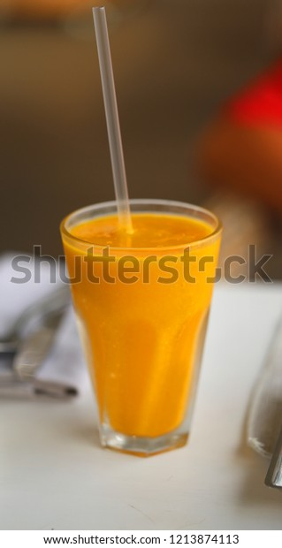 Macro photo of a delicious mango and banana smoothie on a table lit by the sun