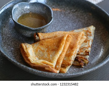 Macro photo of delicious pancakes with honey on a dark plate in a restaurant