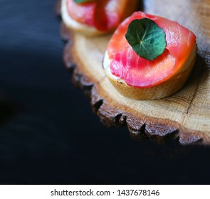 Macro photo of delicious red fish sandwich on wooden background