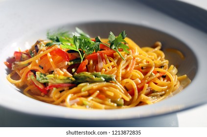 Macro photo of delicious spaghetti with vegetables on a white plate
