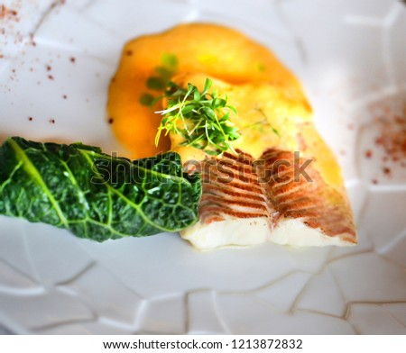 Macro photo of delicious white fish with salad on a plate in a restaurant