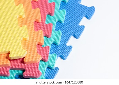 Macro photo of the details of a foam eva isolated on white background. Colored rubber mat puzzle for children.