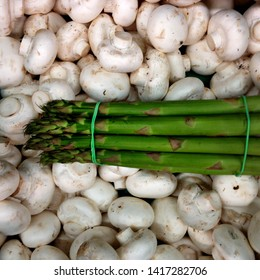 Macro Photo food asparagus and champignon mushrooms. Texture background green stems of fresh asparagus lie on white mushrooms champignons