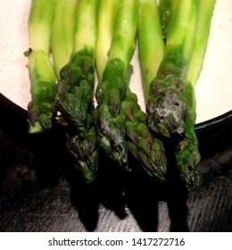 Macro Photo food boiled green asparagus. Texture background peeled asparagus stalks under lemon juice. Image of vegetable cooked asparagus on a plate