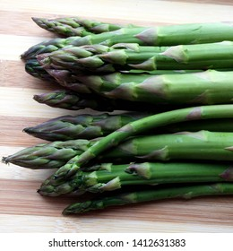 Macro Photo food vegetable asparagus. Texture background of green fresh asparagus sticks. Image of product vegetable stems of green asparagus on wooden board