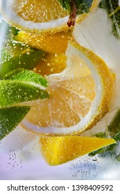 Macro photo of fresh lime and lemon slices with bubbles in the glass. Summer cold drink