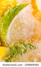 Macro photo of freshly made lemonade with pieces of lime, lemon and bubbles in a glass. Summer refreshing drink
