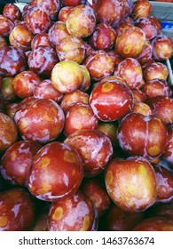 Macro photo of fruit plums. Background of fresh red and yellow plums. Large red-yellow plums on the market, top view.