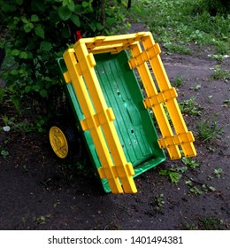 Macro photo garden kids cart. Cart trailer yellow and green. Cart on wheels. The outdoor wagon trolley cart is in the yard.