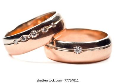 Macro photo of gold wedding rings with diamonds. White background.